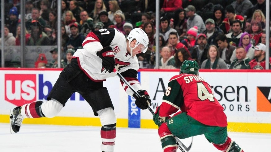Arizona Coyotes left wing Lawson Crouse (67) shoots the puck against Minnesota Wild defenseman Jared Spurgeon (46) during the second period of an NHL hockey game, Saturday, Dec. 17, 2016, in St. Paul, Minn. (AP Photo/Hannah Foslien)