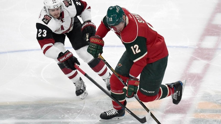 Minnesota Wild center Eric Staal (12) skates with the puck against Arizona Coyotes defenseman Oliver Ekman-Larsson (23), of Sweden, during the first period of an NHL hockey game Saturday, Dec. 17, 2016, in St. Paul, Minn. (AP Photo/Hannah Foslien)