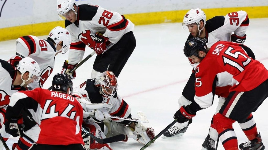New Jersey Devils goaltender Keith Kinkaid (1) keeps his eyes on the puck as Ottawa Senators' Zack Smith (15) prepares to shoot during the third period of an NHL hockey game, Saturday, Dec. 17, 2016 in Ottawa, Ontario. (Fred Chartrand/The Canadian Press via AP)
