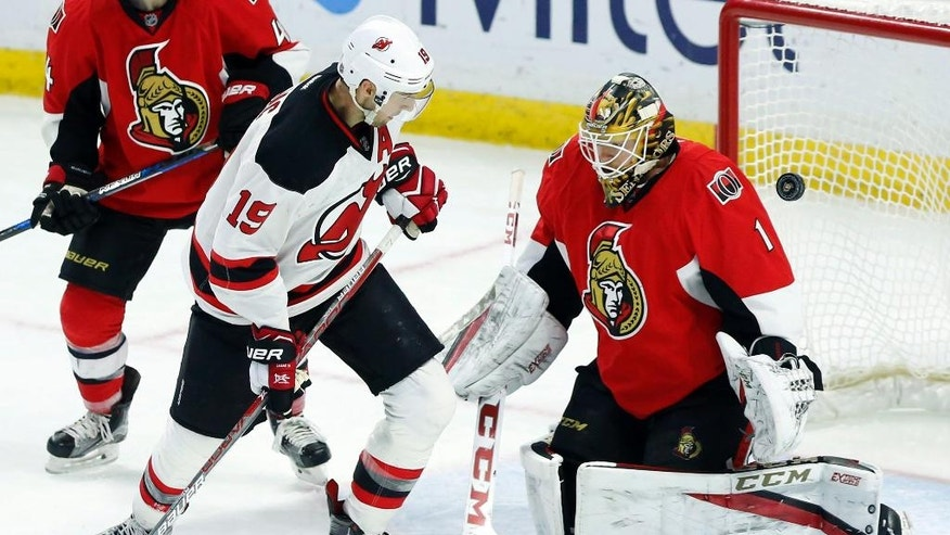Ottawa Senators goaltender Mike Condon (1) makes a save on New Jersey Devils' Travis Zajac (19) during the third period of an NHL hockey game, Saturday, Dec. 17, 2016 in Ottawa, Ontario. (Fred Chartrand/The Canadian Press via AP)