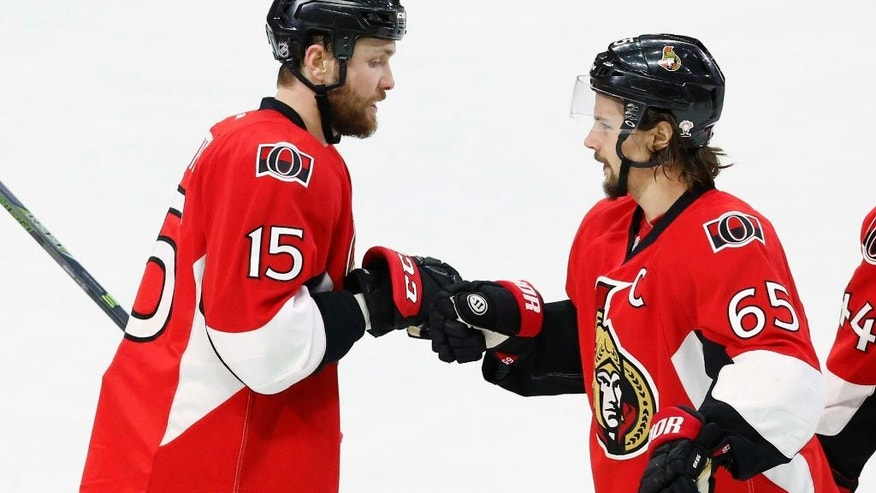 Ottawa Senators' Zack Smith (15) is congratulated by teammate Erik Karlsson (65) after Smith scored on an empty net against the New Jersey Devils during the third period of an NHL hockey game, Saturday, Dec. 17, 2016 in Ottawa, Ontario. (Fred Chartrand/The Canadian Press via AP)
