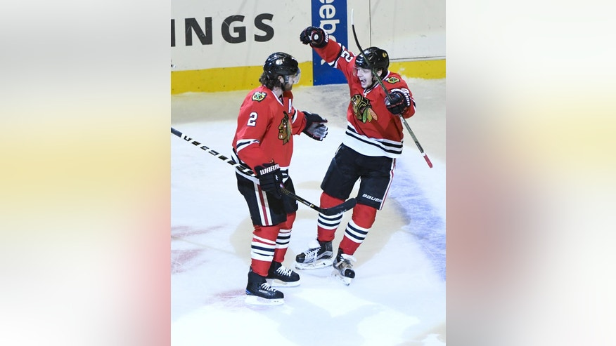 Chicago Blackhawks defenseman Duncan Keith (2) celebrates with Chicago Blackhawks left wing Artemi Panarin, right, after he scored a goal against the San Jose Sharks during the second period of an NHL hockey game on Sunday, Dec. 18, 2016, in Chicago. (AP Photo/Matt Marton)