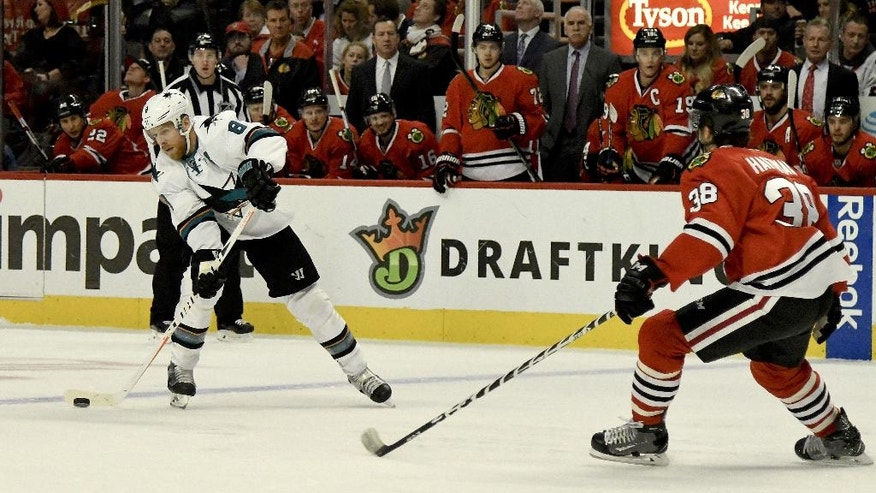 San Jose Sharks center Joe Pavelski (8) passes against Chicago Blackhawks right wing Ryan Hartman (38) during the first period of an NHL hockey game on Sunday, Dec. 18, 2016, in Chicago. (AP Photo/Matt Marton)