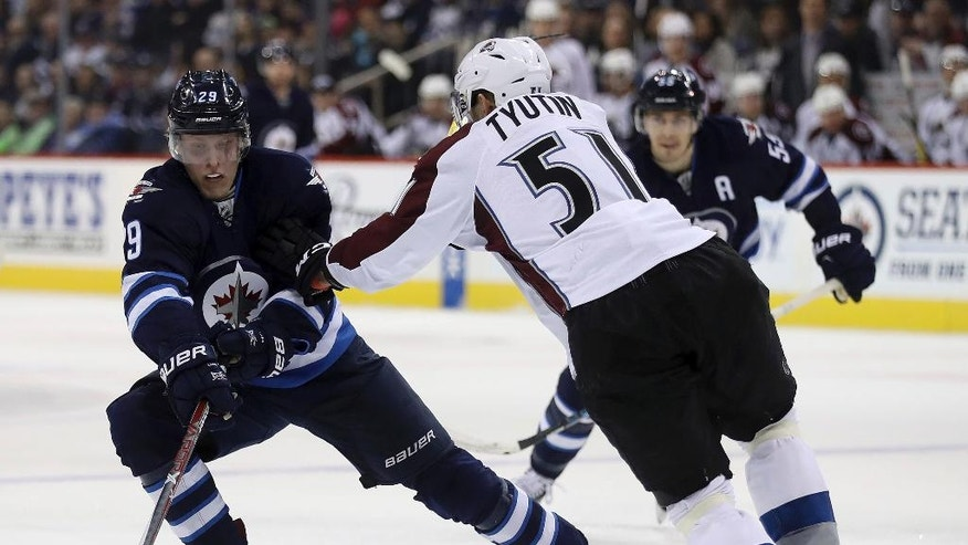 Winnipeg Jets' Patrik Laine (29) uses some fancy moves on Colorado Avalanche's Fedor Tyutin (51)  during the second period of an NHL hockey game, Sunday, Dec. 18, 2016 in Winnipeg, Manitoba. (Trevor Hagan/The Canadian Press via AP)