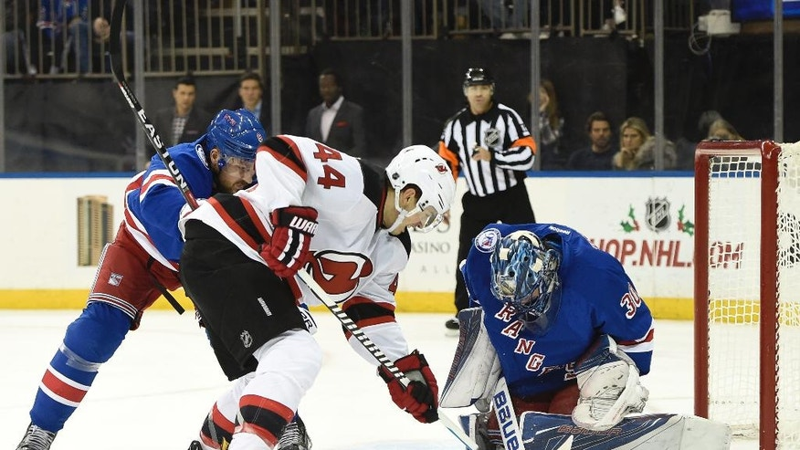 New York Rangers goalie Henrik Lundqvist (30) stops a shot on goal by New Jersey Devils left wing Miles Wood (44) as Rangers defenseman Kevin Klein (8) defends in the first period of an NHL hockey game in New York, Sunday, Dec. 18, 2016. (AP Photo/Kathy Kmonicek)