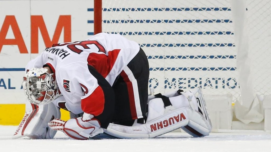 Ottawa Senators goalie Andrew Hammond (30) kneels on the ice after he was hurt during a scrum in the first period of an NHL hockey game against the New York Islanders, Sunday, Dec. 18, 2016, in New York. (AP Photo/Kathy Willens)