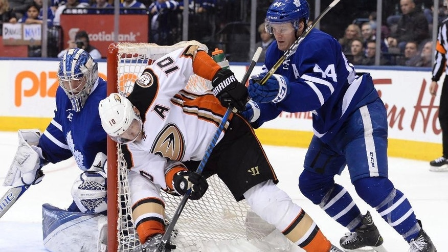Anaheim Ducks right wing Corey Perry (10) plays the puck by the side of the net as Toronto Maple Leafs goalie Frederik Andersen (31) looks on while defenseman Morgan Rielly (44) defends during third period NHL hockey action in Toronto on Monday, Dec. 19, 2016. (Nathan Denette/The Canadian Press via AP)