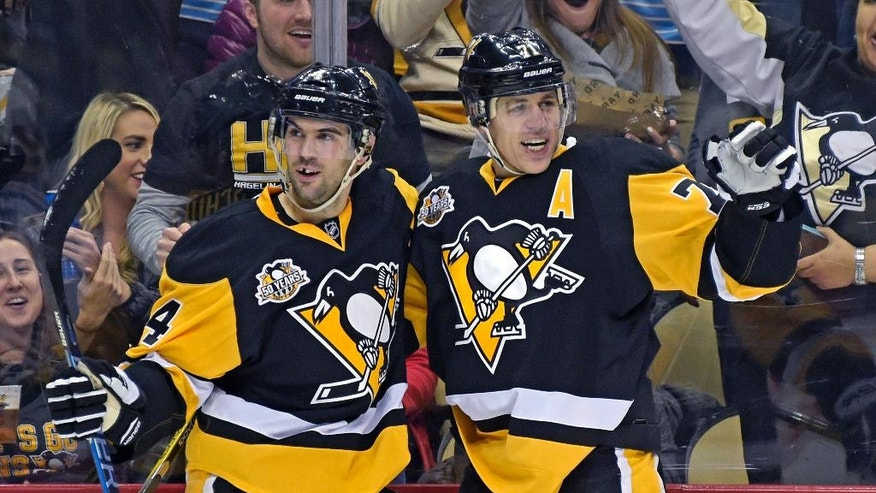 Pittsburgh Penguins defenseman Justin Schultz (4) and center Evgeni Malkin (71) celebrate after Malkin scored a goal during the second period of an NHL hockey game against the New York Rangers on Tuesday, Dec. 20, 2016, in Pittsburgh. The Penguins won 7-2. (AP Photo/Fred Vuich)