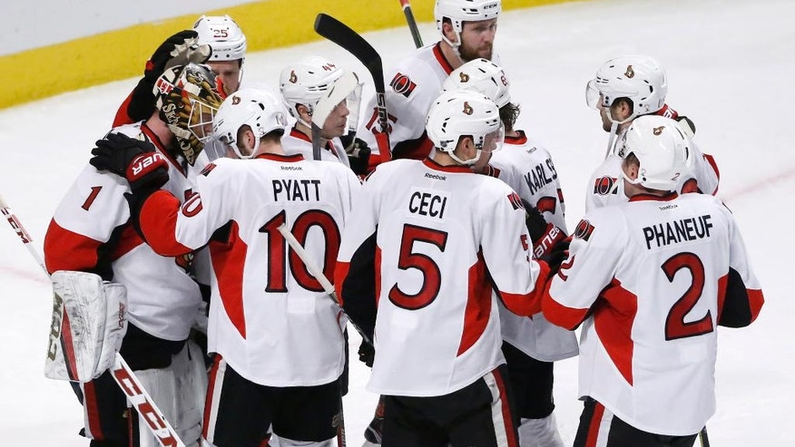 The Ottawa Senators celebrate around goalie Mike Condon (1) after an NHL hockey game against the Chicago Blackhawks, Tuesday, Dec. 20, 2016, in Chicago. The Senators won 4-3. (AP Photo/Charles Rex Arbogast)