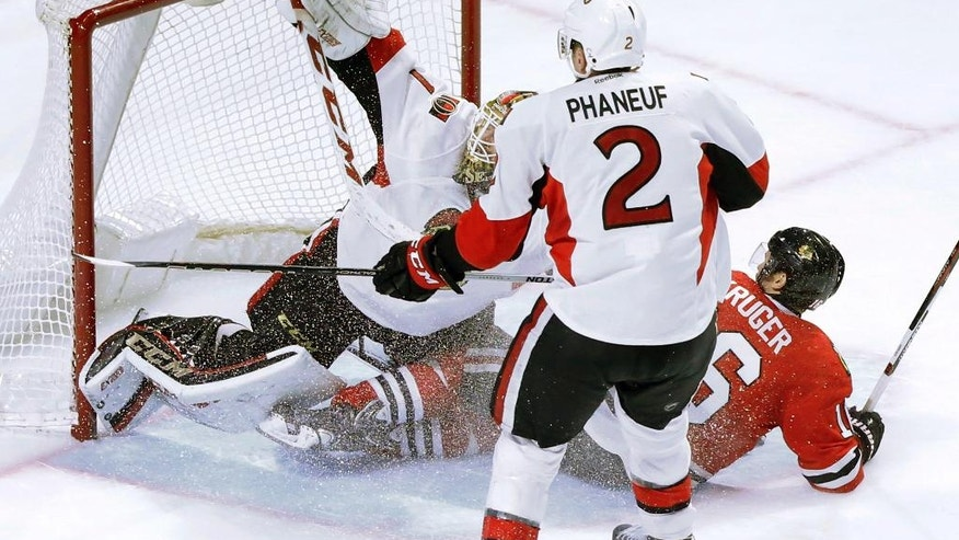 Ottawa Senators goalie Mike Condon, left, makes a pad save on a shot from Chicago Blackhawks' Marcus Kruger, right, as Dion Phaneuf (2) watches during the third period of an NHL hockey game, Tuesday, Dec. 20, 2016, in Chicago. The Senators won 4-3. (AP Photo/Charles Rex Arbogast)