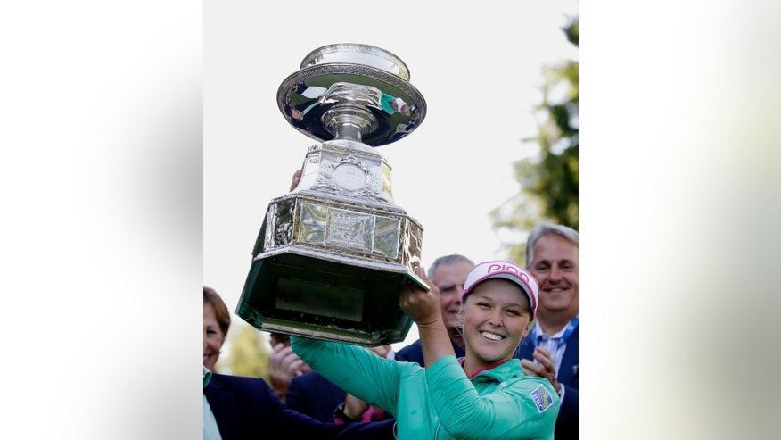 FILE - In this June 12, 2016, file photo, Brooke Henderson, of Canada, lifts the championship trophy after winning the Women's PGA Championship golf tournament at Sahalee Country Club in Sammamish, Wash. (AP Photo/Elaine Thompson, File)