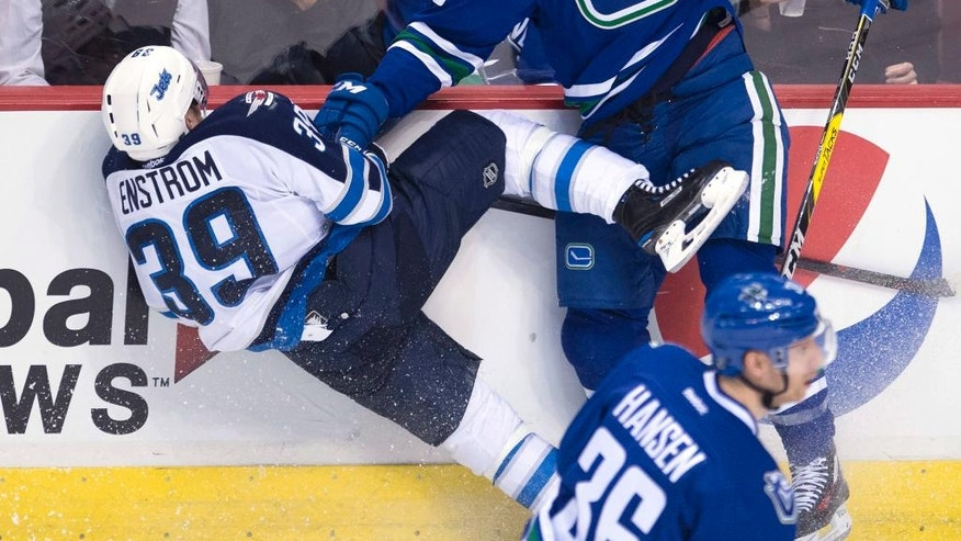 Vancouver Canucks defenseman Alex Biega (55) goes into the boards with Winnipeg Jets defenseman Toby Enstrom (39) during the third period of an NHL hockey game Tuesday, Dec. 20, 2016, in Vancouver, British Columbia. (Jonathan Hayward/The Canadian Press via AP)