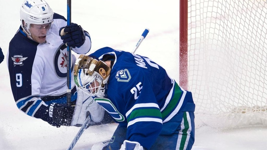 Vancouver Canucks goalie Jacob Markstrom (25) stops a shot from Winnipeg Jets center Andrew Copp (9(  during the third period of an NHL hockey game Tuesday, Dec. 20, 2016, in Vancouver, British Columbia. (Jonathan Hayward/The Canadian Press via AP)