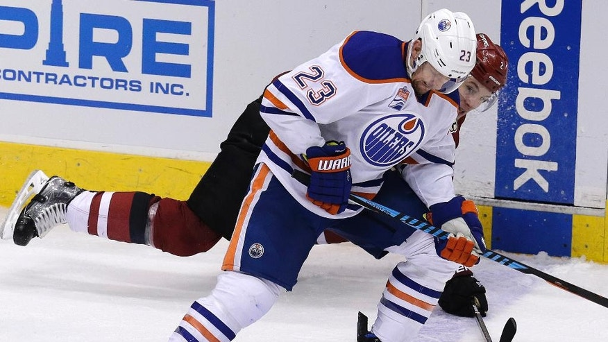 Edmonton Oilers left wing Matt Hendricks (23) shields Arizona Coyotes defenseman Luke Schenn from the puck in the second period during an NHL hockey game, Wednesday, Dec. 21, 2016, in Glendale, Ariz. (AP Photo/Rick Scuteri)