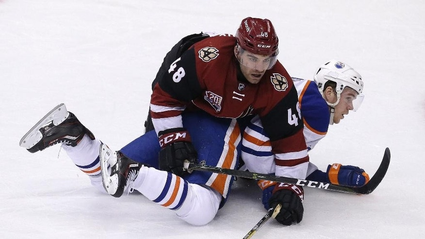 Arizona Coyotes left wing Jordan Martinook (48) holds down Edmonton Oilers center Connor McDavid in the second period during an NHL hockey game, Wednesday, Dec. 21, 2016, in Glendale, Ariz. (AP Photo/Rick Scuteri)