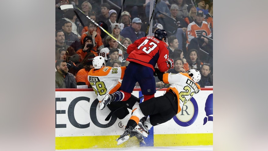 Philadelphia Flyers' Taylor Leier (58) and Brandon Manning (23) collide with Washington Capitals' Tom Wilson (43) during the second period of an NHL hockey game, Wednesday, Dec. 21, 2016, in Philadelphia. (AP Photo/Matt Slocum)
