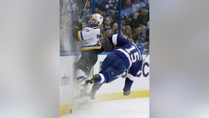 Tampa Bay Lightning left wing Michael Bournival (15) goes airborne as he checks St. Louis Blues defenseman Brad Hunt (77) into the boards during the second period of an NHL hockey game Thursday, Dec. 22, 2016, in Tampa, Fla. (AP Photo/Chris O'Meara)