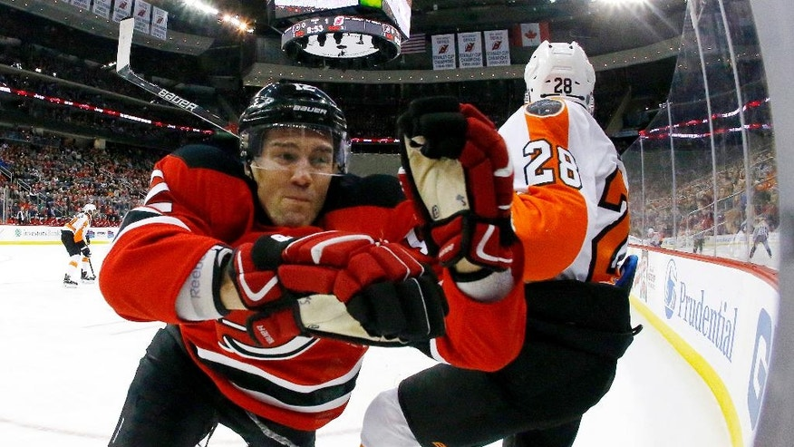 New Jersey Devils defenseman Ben Lovejoy, left, goes flying into the boards while applying pressure on Philadelphia Flyers center Claude Giroux during the first period of an NHL hockey game, Thursday, Dec. 22, 2016, in Newark, N.J. (AP Photo/Julio Cortez)