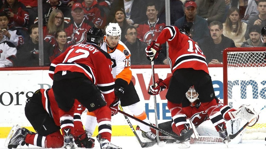 New Jersey Devils goalie Cory Schneider, bottom right, tries to block a shot as teammates defend against Philadelphia Flyers center Chris VandeVelde (76) during the first second of an NHL hockey game, Thursday, Dec. 22, 2016, in Newark, N.J. (AP Photo/Julio Cortez)