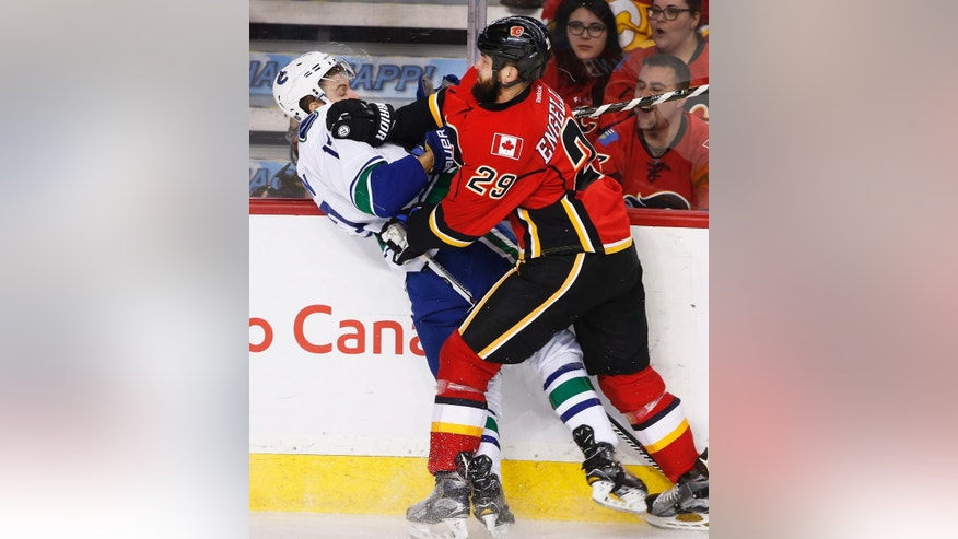 Vancouver Canucks' Anton Rodin, left, of Sweden, takes a hit from Calgary Flames' Deryk Engelland during second-period NHL hockey game action in Calgary, Alberta, Friday, Dec. 23, 2016. (Larry MacDougal/The Canadian Press via AP)