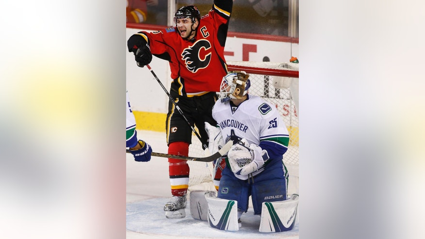 Calgary Flames' Mark Giordano, left, celebrates his goal against Vancouver Canucks goalie Jacob Markstrom, of Sweden, during second-period NHL hockey game action in Calgary, Alberta, Friday, Dec. 23, 2016. (Larry MacDougal/The Canadian Press via AP)