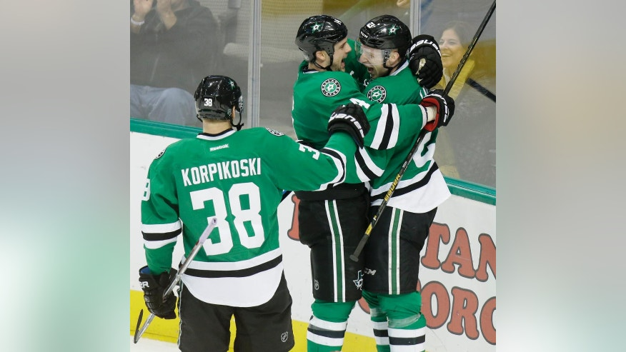 Dallas Stars defenseman Esa Lindell (23) celebrates his game-winning goal with teammates Jamie Benn (14) and Lauri Korpikoski (38) during overtime in an NHL hockey game against the Los Angeles Kings in Dallas, Friday, Dec. 23, 2016. The Stars won 3-2. (AP Photo/LM Otero)