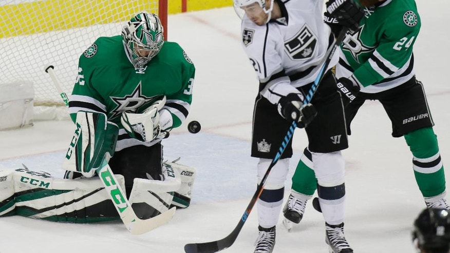 Dallas Stars goalie Kari Lehtonen (32) blocks a shot in front of Los Angeles Kings center Nick Shore (21) and Stars defenseman Jordie Benn (24) during the second period of an NHL hockey game in Dallas, Friday, Dec. 23, 2016. The Stars won 3-2 in overtime. (AP Photo/LM Otero)