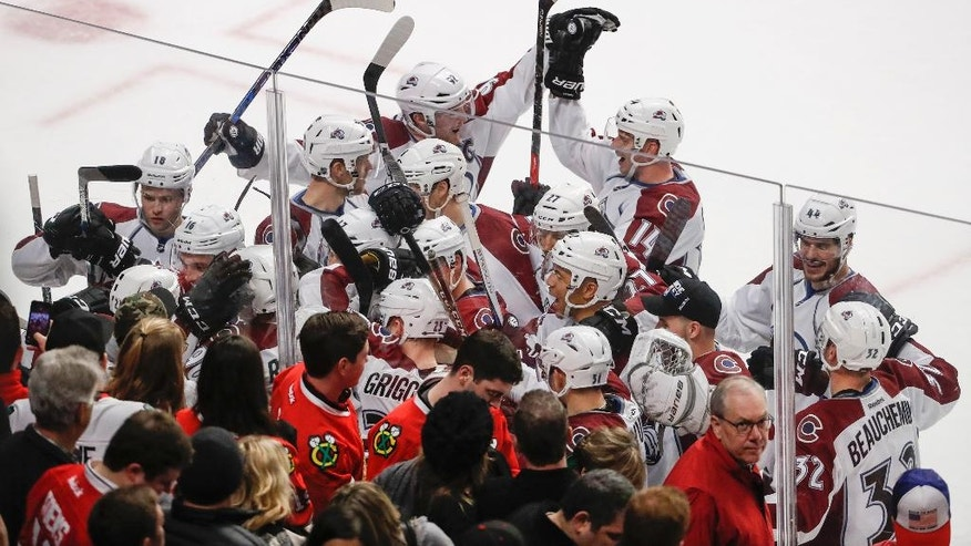 Colorado Avalanche players celebrate a 2-1 overtime win against the Chicago Blackhawks during an NHL hockey game Friday, Dec. 23, 2016, in Chicago. (AP Photo/Kamil Krzaczynski)