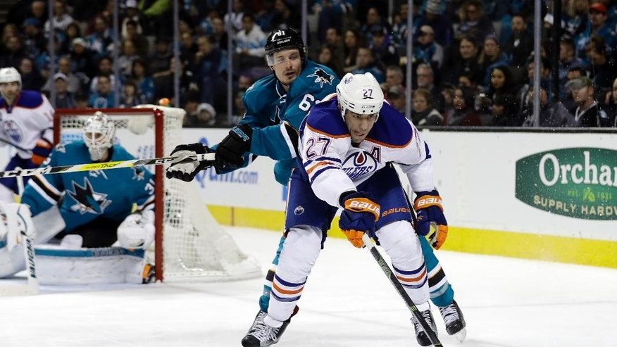 Edmonton Oilers' Milan Lucic (27) is defended by San Jose Sharks' Justin Braun (61) during the second period of an NHL hockey game Friday, Dec. 23, 2016, in San Jose, Calif. (AP Photo/Marcio Jose Sanchez)