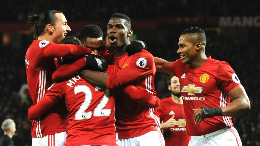 Manchester United players celebrate after Manchester United's Henrikh Mkhitaryan, second left, after scored his side third goal during the English Premier League soccer match between Manchester United and Sunderland at Old Trafford in Manchester, England, Monday, Dec. 26, 2016. (AP Photo/Rui Vieira)
