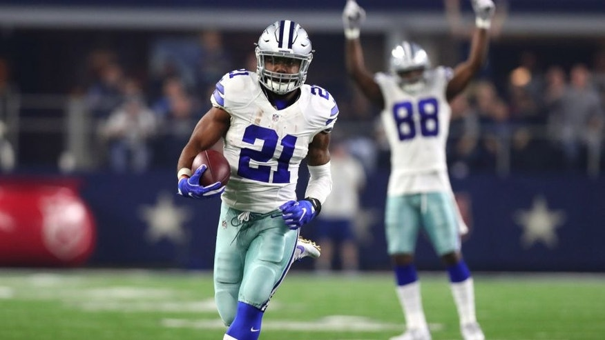 ARLINGTON, TX - DECEMBER 26: Ezekiel Elliott #21 of the Dallas Cowboys runs for a touchdown as teammate Dez Bryant #88 celebrates as the Cowboys play the Detroit Lions during the first half at AT&T Stadium on December 26, 2016 in Arlington, Texas. (Photo by Tom Pennington/Getty Images)