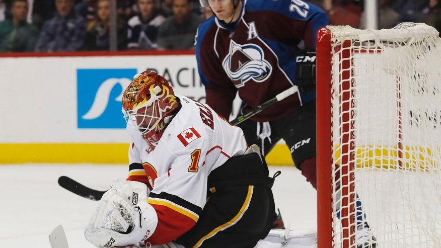 Calgary Flames goalie Brian Elliott, front, makes a kick save of a shot as Colorado Avalanche center Nathan MacKinnon looks on in the first period of an NHL hockey game, Tuesday, Dec. 27, 2016, in Denver. (AP Photo/David Zalubowski)