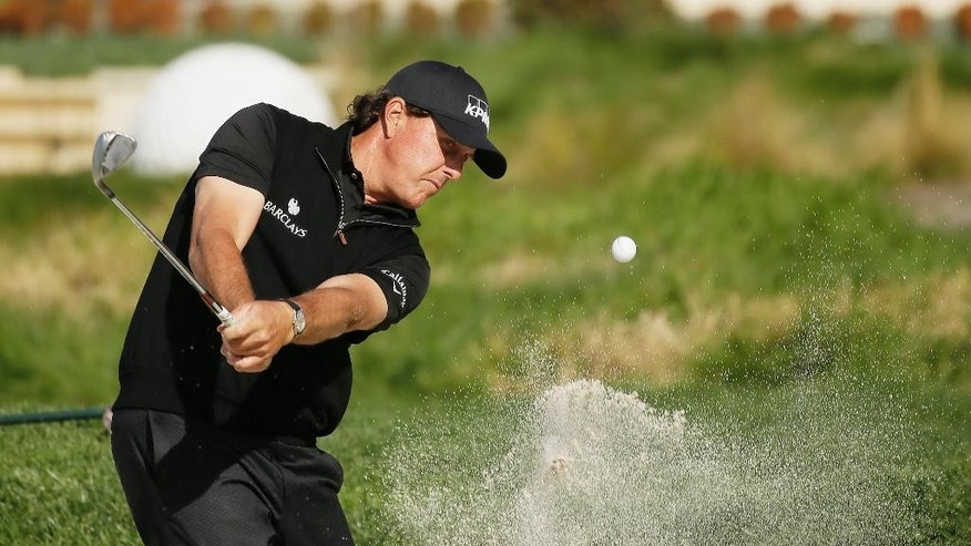 FILE - In a Sunday, Feb. 14, 2016 file photo, Phil Mickelson hits out of a bunker onto the second green of the Pebble Beach Golf Links during the final round of the AT&T Pebble Beach National Pro-Am golf tournament, in Pebble Beach, Calif. (AP Photo/Eric Risberg)