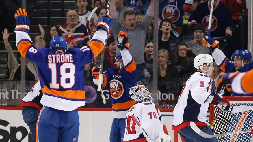New York Islanders' Ryan Strome, (18), Cal Clutterbuck, center, and others celebrate after Clutterbuck scored a goal on Washington Capitals' goalie Braden Holtby (70) during the first period of an NHL hockey game, Tuesday, Dec. 27, 2016, in New York. (AP Photo/Kathy Willens)
