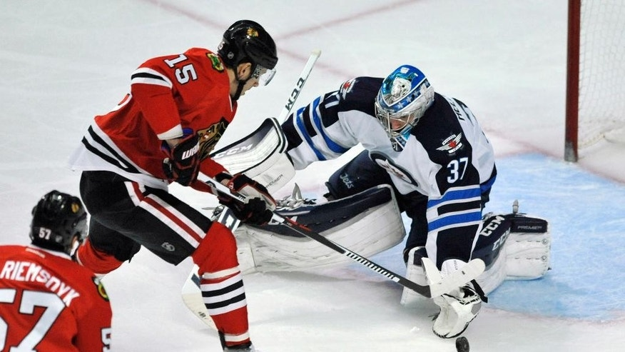 Chicago Blackhawks' Artem Anisimov (15) of Russia, scores a goal against Winnipeg Jets goalie Connor Hellebuyck (37) during the second period of an NHL hockey game Tuesday, Dec. 27, 2016, in Chicago. (AP Photo/Paul Beaty)