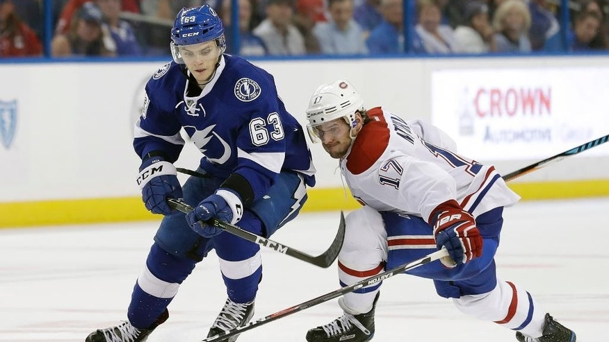 Tampa Bay Lightning center Matthew Peca (63) skates around Montreal Canadiens center Torrey Mitchell (17) during the second period of an NHL hockey game Wednesday, Dec. 28, 2016, in Tampa, Fla. (AP Photo/Chris O'Meara)