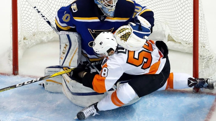 Philadelphia Flyers' Taylor Leier (58) slides into St. Louis Blues goalie Carter Hutton during the second period of an NHL hockey game, Wednesday, Dec. 28, 2016, in St. Louis. (AP Photo/Jeff Roberson)