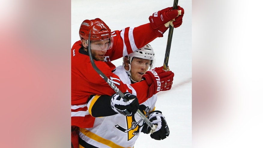 Carolina Hurricanes' Jordan Staal (11) battles for position with Pittsburgh Penguins' Chad Ruhwedel (2) during the first period of an NHL hockey game in Pittsburgh, Wednesday, Dec. 28, 2016. (AP Photo/Gene J. Puskar)