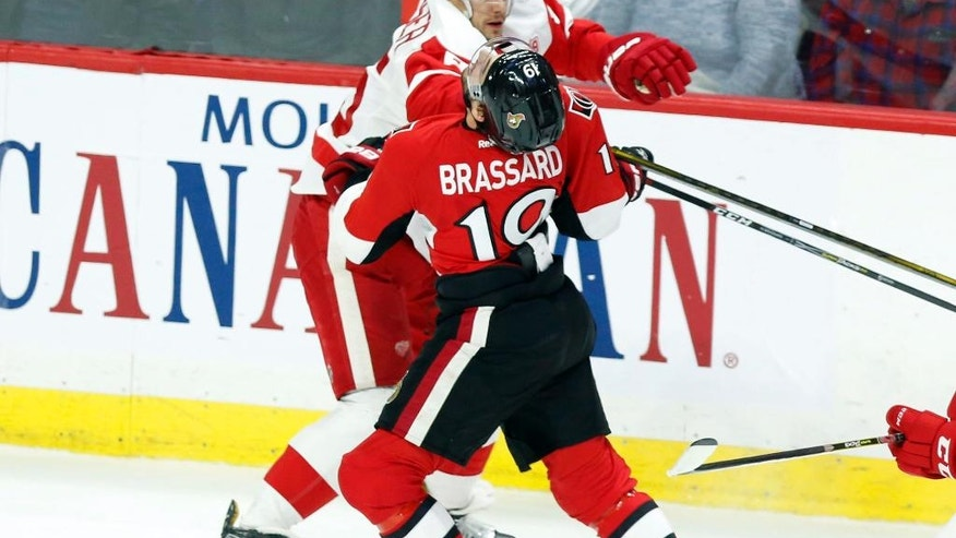 Ottawa Senators' Derick Brassard (19) runs into Detroit Red Wings' Danny DeKeyser (65) during the first period of an NHL hockey game in Ottawa, Ontario, Thursday Dec. 29, 2016.  (Fred Chartrand/The Canadian Press via AP)