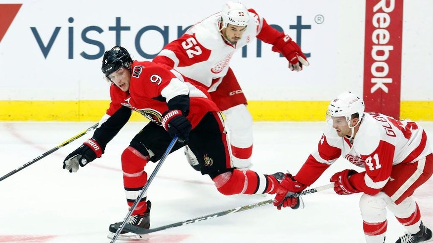Ottawa Senators' Bobby Ryan (9) attempts to reach for the puck as Detroit Red Wings' Luke Glendening (41) and Jonathan Ericsson (52) close in during the first period of an NHL hockey game in Ottawa, Ontario, Thursday Dec. 29, 2016.  (Fred Chartrand/The Canadian Press via AP)
