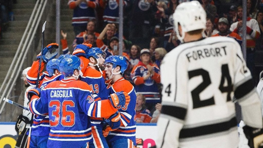 Edmonton Oilers players celebrate a goal as Los Angeles Kings' Derek Forbort (24) skates by during the second period of an NHL hockey game in Edmonton, Alberta, Thursday, Dec. 29, 2016. (Jason Franson/The Canadian Press via AP)