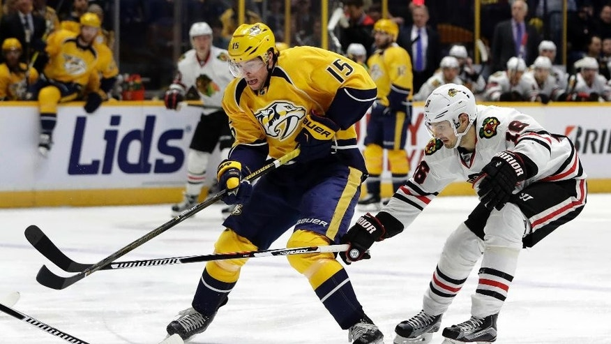 Nashville Predators right wing Craig Smith (15) battles for the puck with Chicago Blackhawks center Marcus Kruger (16), of Sweden, during the second period of an NHL hockey game Thursday, Dec. 29, 2016, in Nashville, Tenn. (AP Photo/Mark Humphrey)