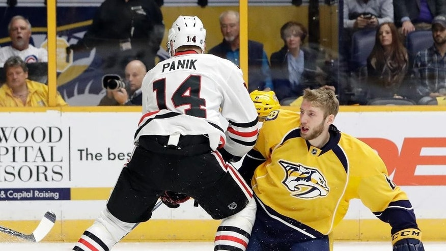 Nashville Predators defenseman Petter Granberg, of Sweden, right, loses his helmet as he battles Chicago Blackhawks left wing Richard Panik (14), of Slovakia, for the puck during the first period of an NHL hockey game Thursday, Dec. 29, 2016, in Nashville, Tenn. (AP Photo/Mark Humphrey)