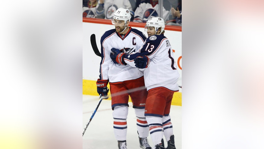 Columbus Blue Jackets' Nick Foligno (71) and Cam Atkinson (13) celebrate Foligno's goal against the Winnipeg Jets during the first period of an NHL hockey game Thursday, Dec. 29, 2016, in Winnipeg, Manitoba. (John Woods/The Canadian Press via AP)