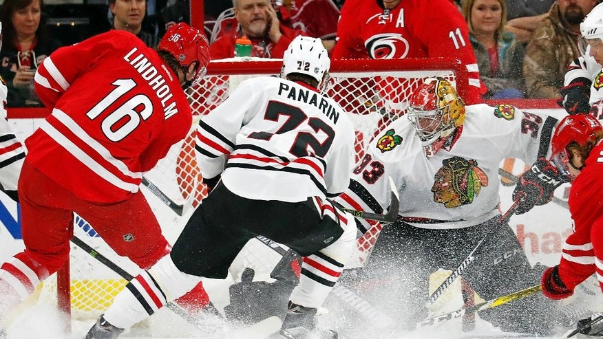 Carolina Hurricanes' Elias Lindholm (16) slips the puck past Chicago Blackhawks goalie Scott Darling (33) with Artemi Panarin (72) nearby for a goal during the first period of an NHL hockey game, Friday, Dec. 30, 2016, in Raleigh, N.C. (AP Photo/Karl B DeBlaker)