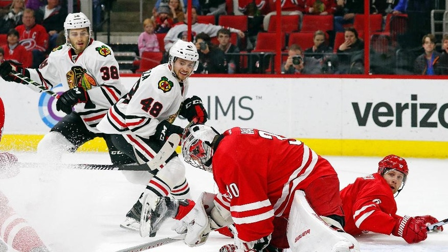 Carolina Hurricanes goalie Cam Ward (30) freezes the puck after it is shot by Chicago Blackhawks' Vinnie Hinostroza (48) with Hawks Ryan Hartman (38) looking on during the first period of an NHL hockey game, Friday, Dec. 30, 2016, in Raleigh, N.C. (AP Photo/Karl B DeBlaker)