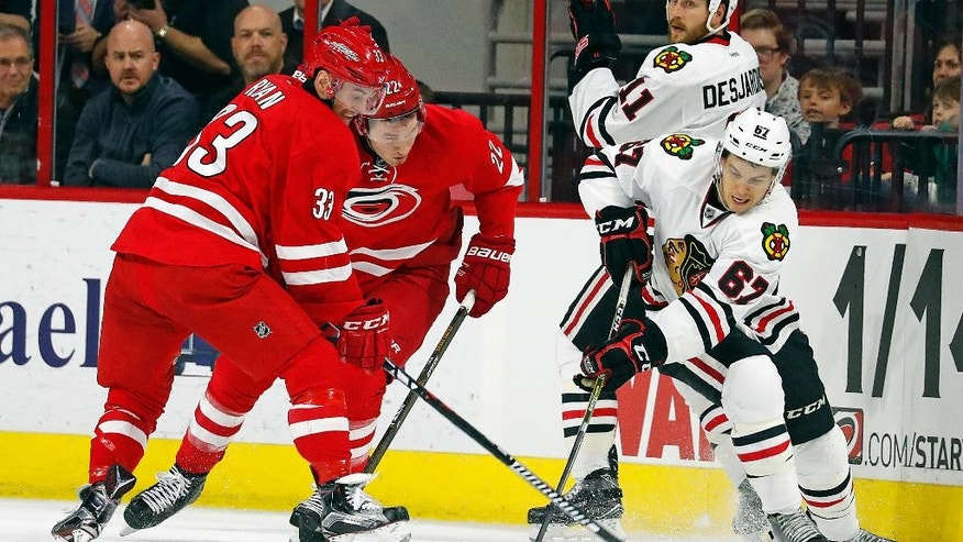 Chicago Blackhawks' Tanner Kero (67) battles with Carolina Hurricanes' Derek Ryan (33) and Brett Pesce (22) during the first period of an NHL hockey game, Friday, Dec. 30, 2016, in Raleigh, N.C. (AP Photo/Karl B DeBlaker)