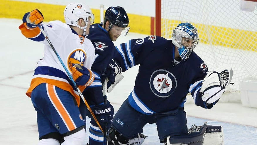 Winnipeg Jets goaltender Connor Hellebuyck (37) saves the shot from New York Islanders' Casey Cizikas (53) as Jets' Paul Postma (4) defends during the first period of an NHL hockey game Saturday, Dec. 31, 2016, in Winnipeg, Manitoba. (John Woods/The Canadian Press via AP)