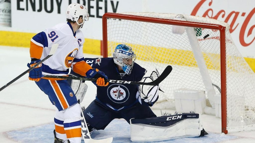 New York Islanders' John Tavares (91) scores on Winnipeg Jets goaltender Connor Hellebuyck (37) during the first period of an NHL hockey game Saturday, Dec. 31, 2016, in Winnipeg, Manitoba. (John Woods/The Canadian Press via AP)