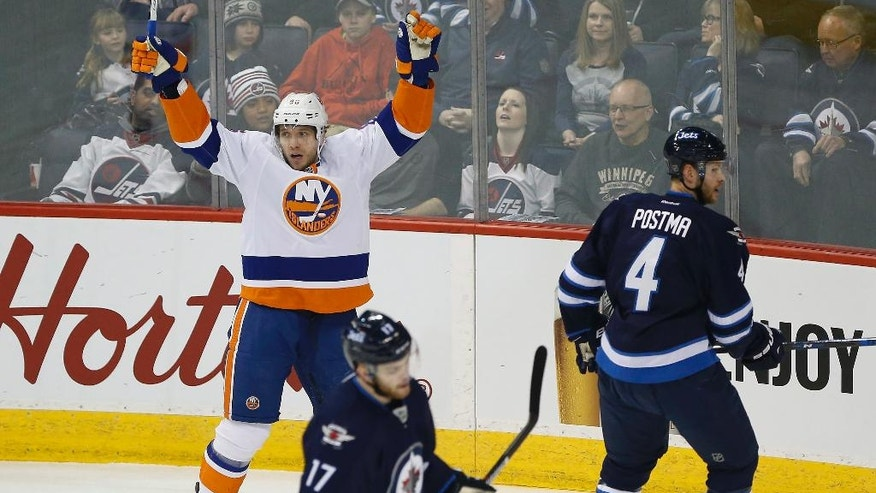 New York Islanders' Nikolay Kulemin (86) celebrates after scoring on Winnipeg Jets goaltender Connor Hellebuyck (37) as Paul Postma (4) and Adam Lowry (17) during the first period of an NHL hockey game Saturday, Dec. 31, 2016, in Winnipeg, Manitoba. (John Woods/The Canadian Press via AP)